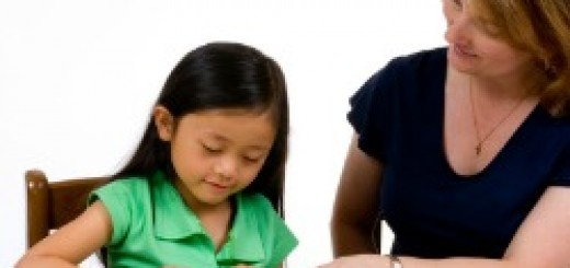 A young girl learns to write with the help of a teacher.
